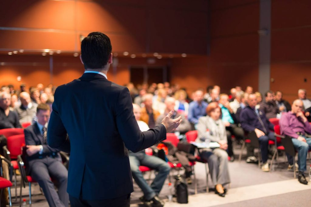 A-man-speaking-at-a-business-conference-499517325_3000x2000